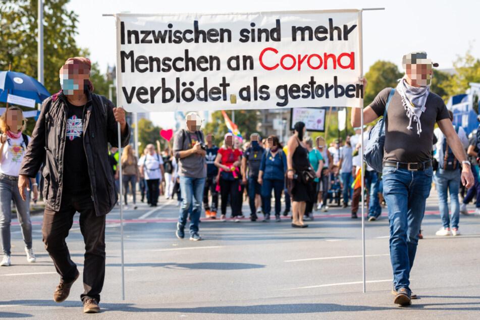 """""""Inzwischen sind mehr Menschen an Corona verblödet als gestorben"""" ist auf einem Plakat der Demonstranten zu lesen."""