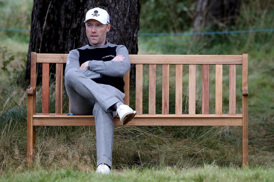 Ronan Keating, Golfer und Popsänger aus Irland, wartet auf einer Bank.