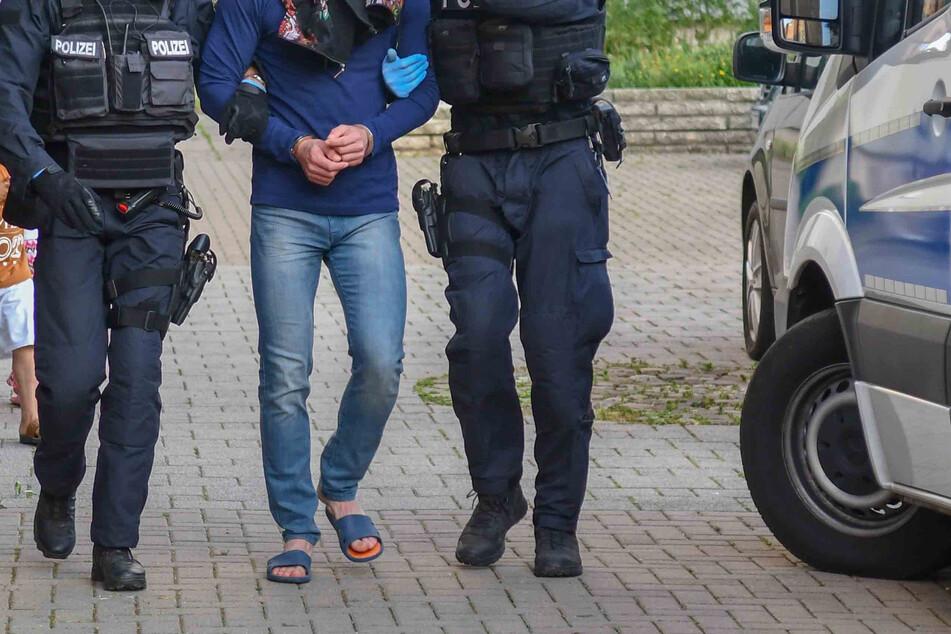 Bewaffnete Polizisten führen während einer Drogenrazzia einen Mann ab. Im Norden gab es mehrere Festnahmen. (Symbolbild)