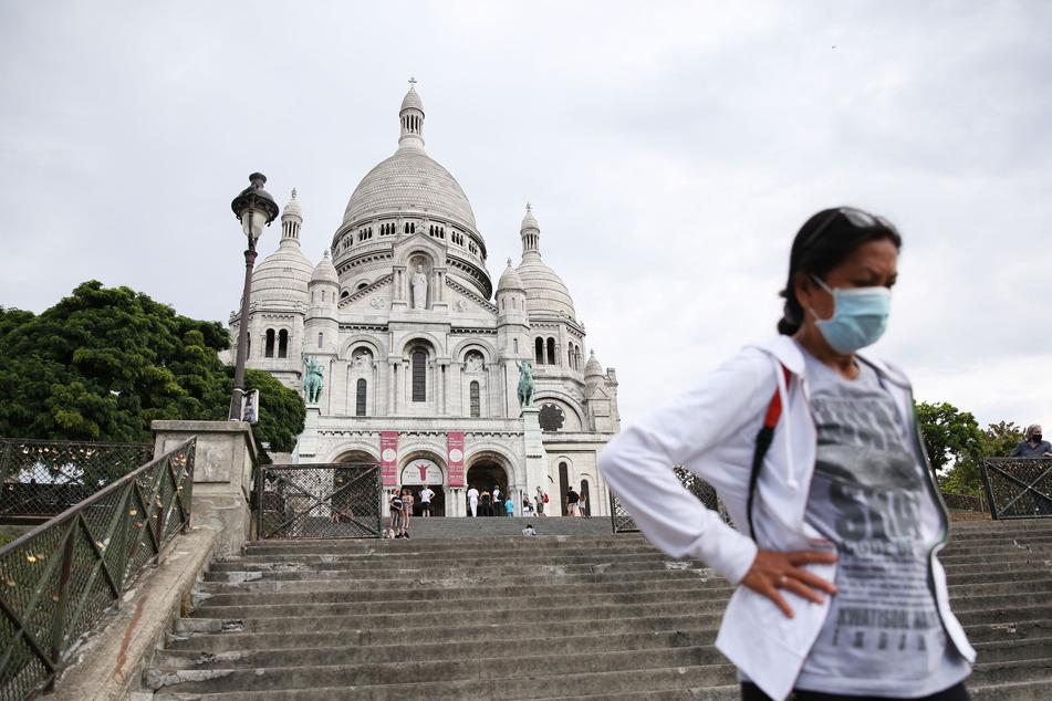Eine Frau steigt die Stufen vor der Basilika Sacre-Coeur auf dem Montmartre hinab.