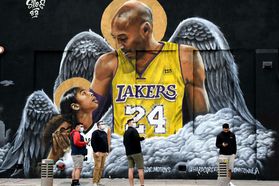 Fans pause beside a mural of Kobe Bryant (†41) and his daughter Gianna (†13) in Downtown LA.