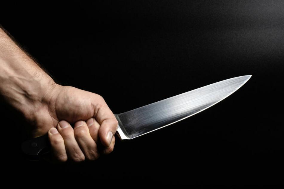 Mann hält eine Küchenmesser in der Hand (Symbolbild).