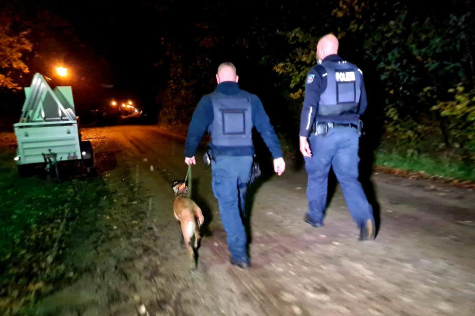 Polizisten suchen mit einem Fährtenhund die Umgebung ab.