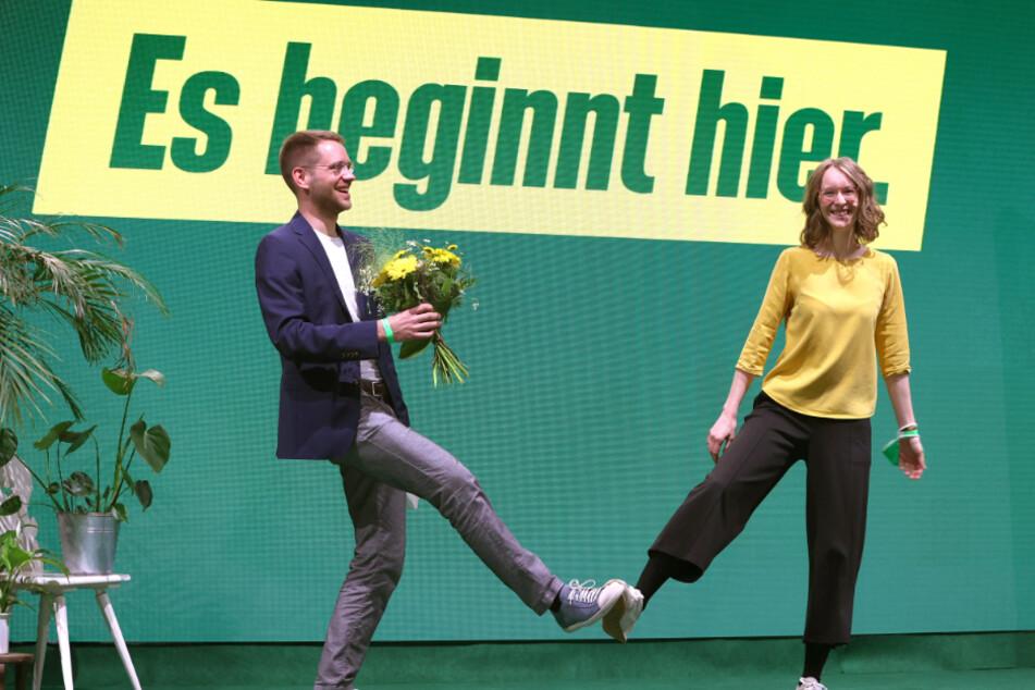 Thomas von Sarnowski (33), neu gewählter Landesvorsitzender Bündnis 90/Die Grünen Bayern, steht nach seiner Wahl neben Eva Lettenbauer (28), ebenso Landesvorsitzende der bayerischen Grünen, mit Blumen auf der Bühne.