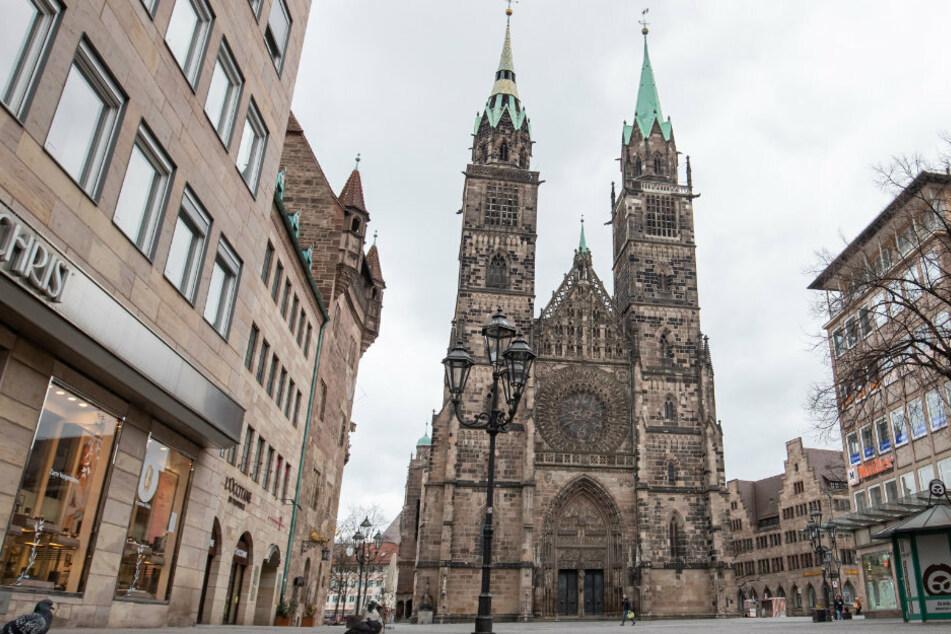 Bayern, Nürnberg: Die sonst am Wochenende gut besuchte Innenstadt, hier die Einkaufstraße Karolinenstraße mit der Lorenzkirche im Hintergrund, bleibt gegen 12:00 Uhr so gut wie leer.