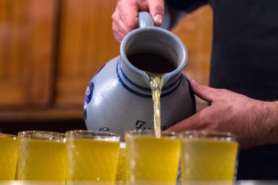 """Ein Apfelwein-Glas (Geripptes) wird im Traditionslokal """"Gemaltes Haus"""" mit einem Krug (Bembel) gefüllt."""