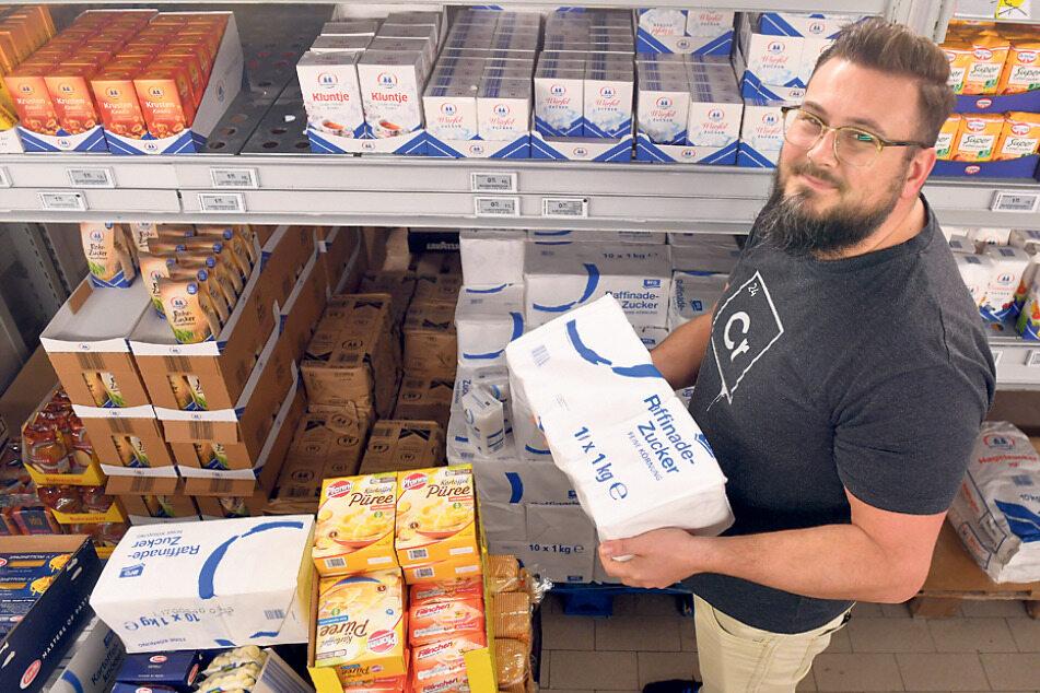 """Zucker, Kartoffelpüree, Nudeln, Toastbrot - Arche-Leiter Marcel Bretschneider füllt den Einkaufswagen mit Lebensmittel für die Familien der """"Arche""""-Kinder."""
