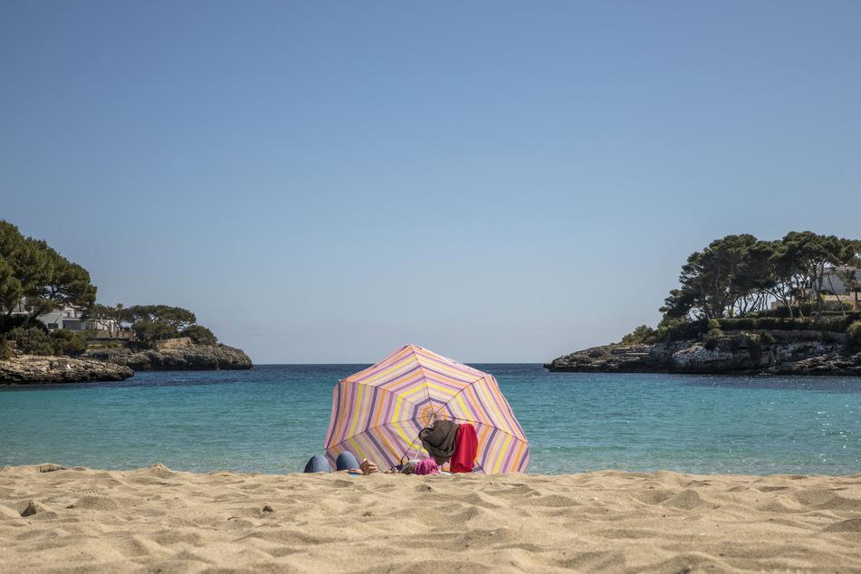 So sieht es aktuell aus: Zwei Personen liegen an einem Strand auf Mallorca.
