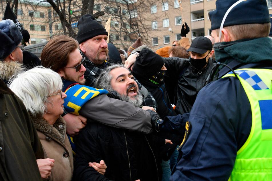 Menschen demonstrieren in Schweden ohne Mund-Nasen-Schutz gegen die Corona-Beschränkungen des Landes und treffen auf Polizisten.