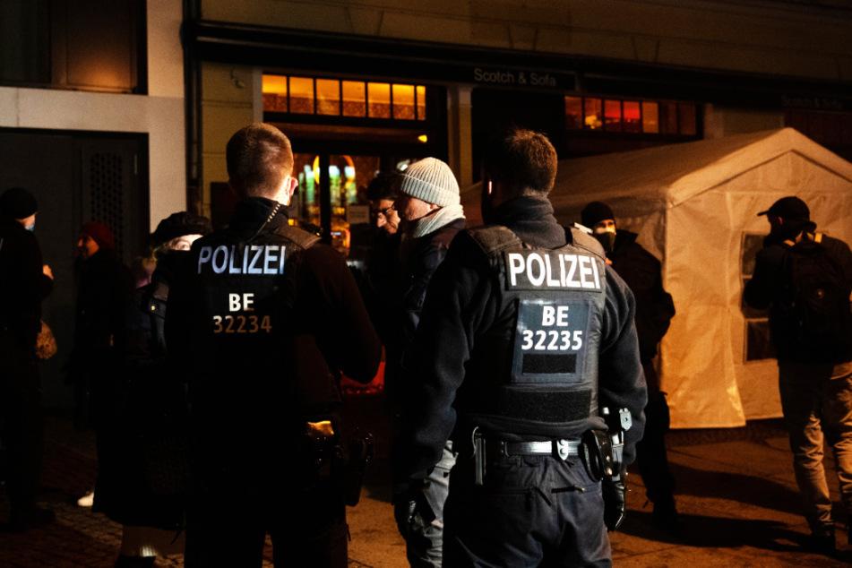 Polizisten und Passanten stehen an der Kollwitzstraße vor einem gastronomischen Betrieb. Wegen des Verstoßes gegen Corona-Regeln war die Berliner Polizei am Donnerstagabend in einem Lokal im Berliner Stadtteil Prenzlauer Berg im Einsatz.