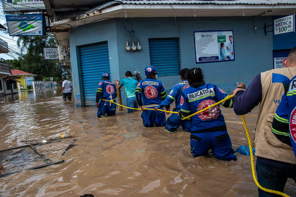 An El Salvadorian rescue team navigates through a flooded street.