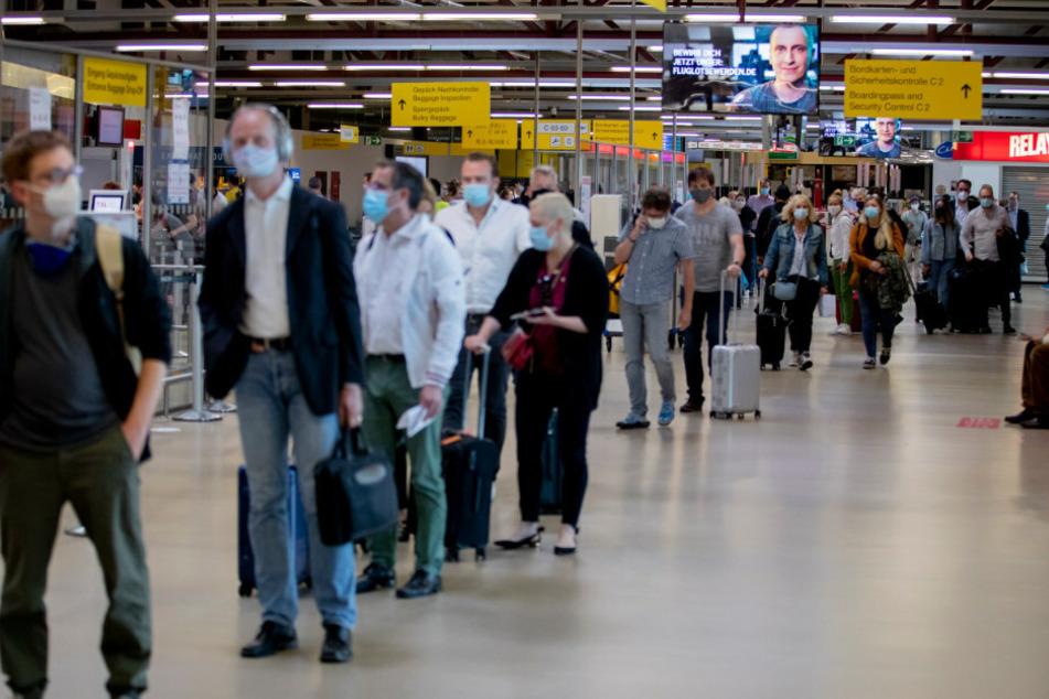 Passagiere stehen am Flughafen Berlin-Tegel vor der Sicherheitskontrolle Schlange.