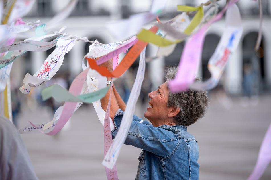 Eine Frau knotet Stoffbänder mit Wünschen, Sprüchen und Parolen an eine Leine vor dem Hamburger Rathaus.