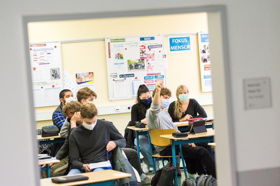 Schüler einer 13.Klasse sitzen mit Mund-Nasen-Bedeckungen im Deutsch-Unterricht.