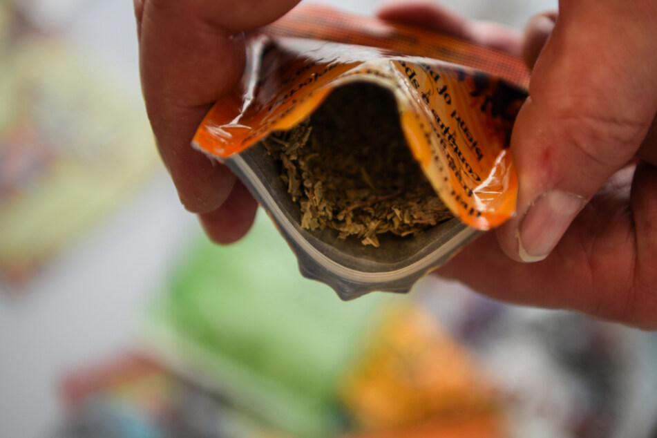 Ein Mitarbeiter des Bundeskriminalamts (BKA) zeigt eine Kräutermischung, die mit einer drogenähnlichen Substanz imprägniert wurde. (Archiv)