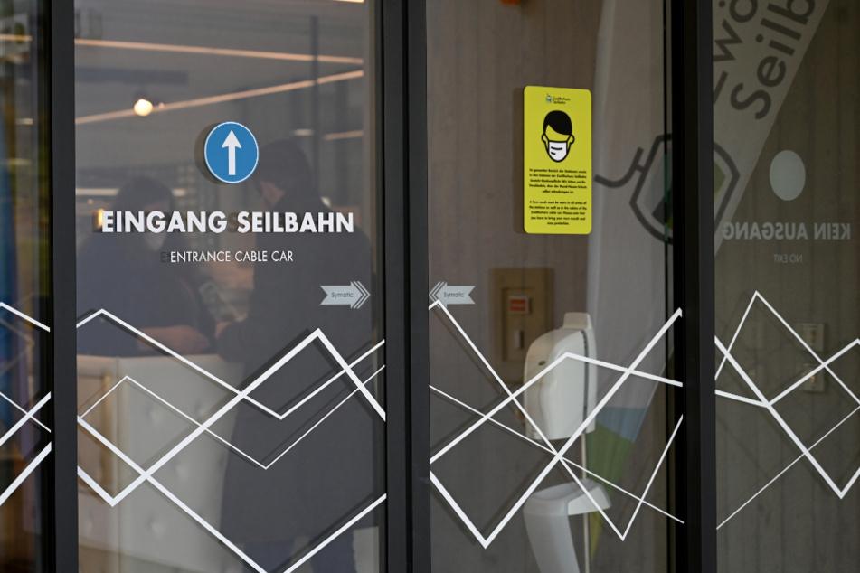 Ein Spender mit Desinfektionsflüssigkeit und ein Hinweisschild zur Maskenpflicht sind im Kassenbereich einer Seilbahn angebracht. Die Zahl der Corona-Fälle in Österreich steigt weiter an.