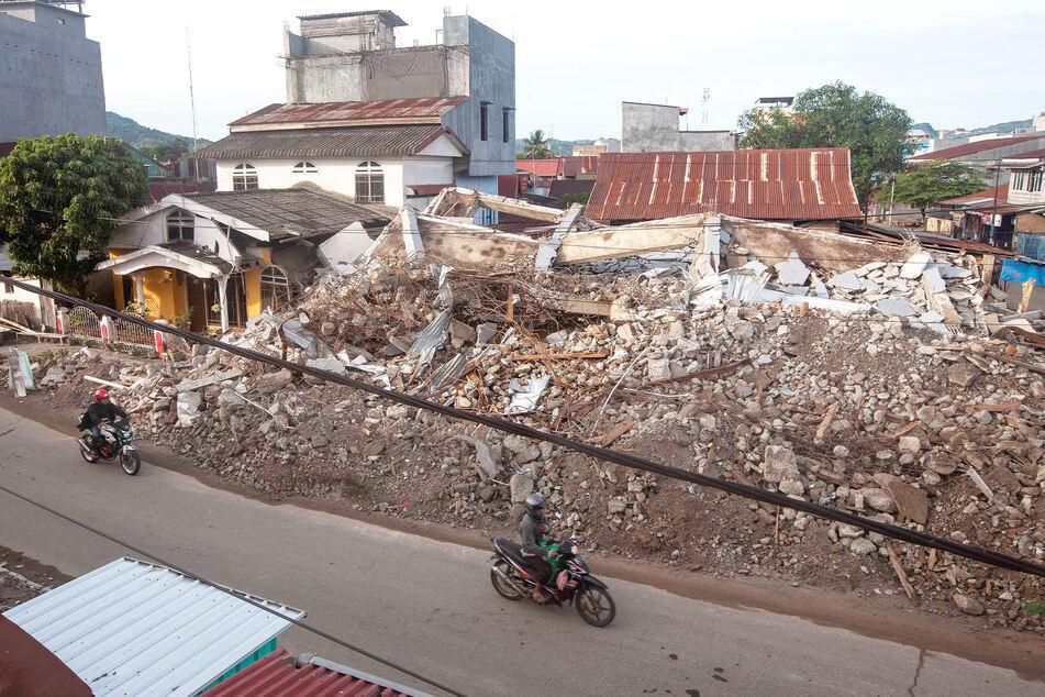 Rollerfahrer fahren an Gebäuden vorbei, die bei einem Erdbeben eingestürzt sind.