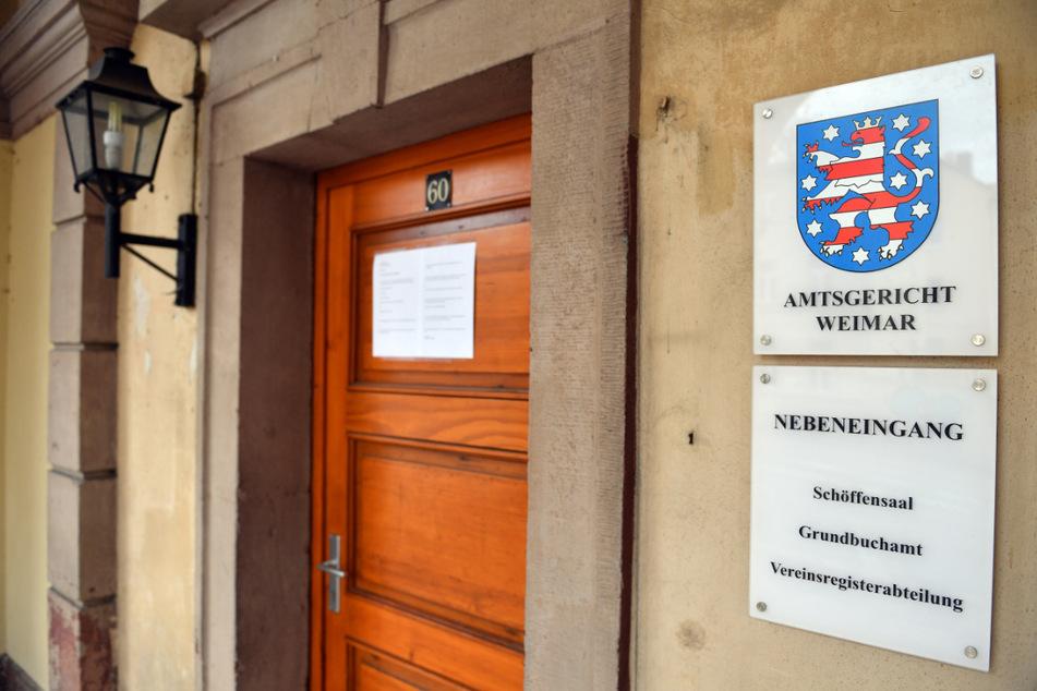 """Das Behördenschild mit der Aufschrift """"Amtsgericht Weimar"""" ist am Amtsgericht in Weimar zu sehen. Der Richter, der ein umstrittenes Urteil zur Maskenpflicht an zwei Thüringer Schulen gefällt hat, steht nun selbst im Fokus der Justiz. (Archivbild)"""
