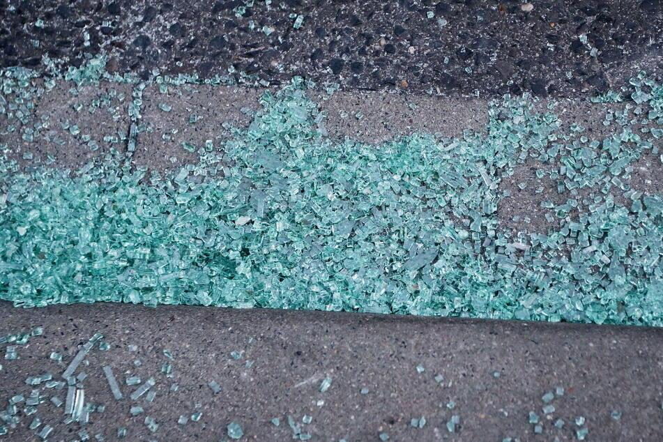 Glasscherben einer Autoscheibe liegen auf einem Gehweg. Sie stammen nach einer Zeugenaussage von einem Auto, in dem zwei Männer von einem MEK der Polizei festgenommen wurden.