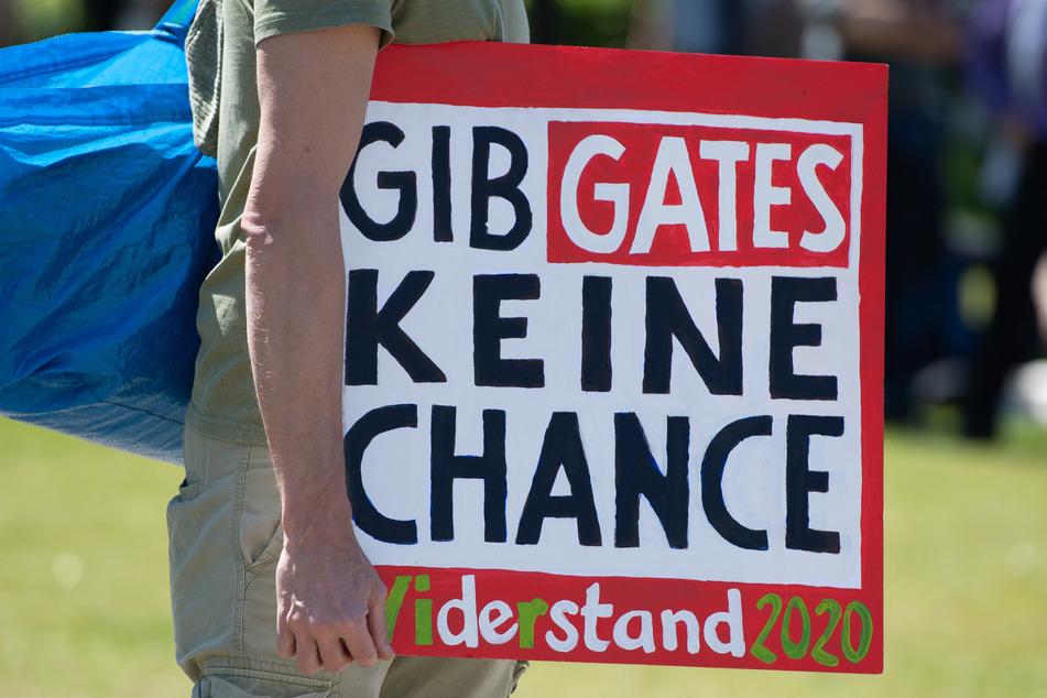 """Bei einer Demonstration vor dem Reichstagsgebäude hält ein Teilnehmer ein Schild mit der Aufschrift """"Gib Gates keine Chance - Widerstand 2020"""". In vielen deutschen Städten versammeln sich derzeit Menschen, die ihr Protest etwa gegen die behördlich verordneten Kontaktsperren auf die Straße treibt."""
