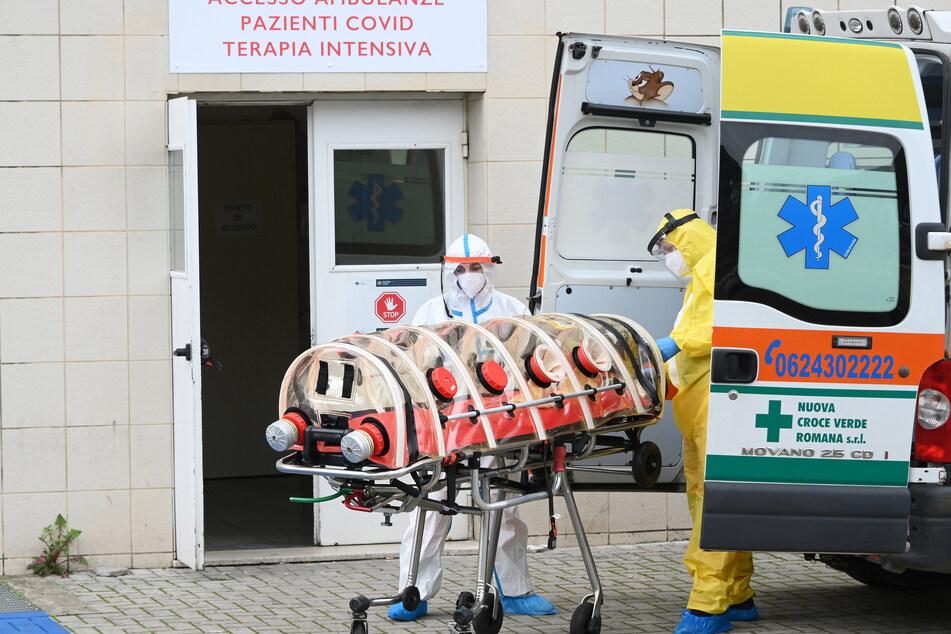 Mitarbeiter in Schutzkleidung stehen vor einem Krankenhaus in Italien - die Zahl der Corona-Toten steigt in dem südeuropäischen Land wieder an.
