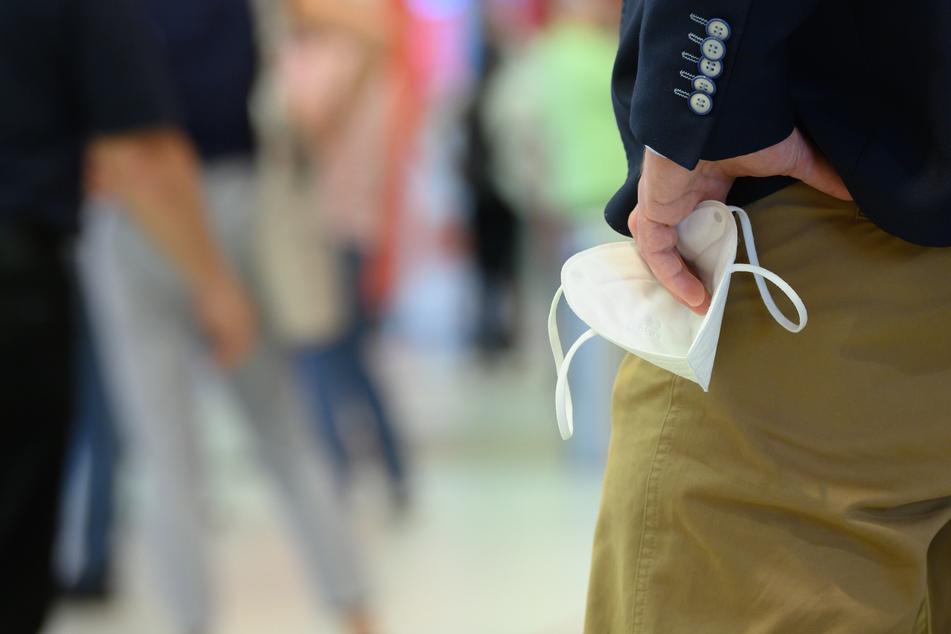 Ein Mann hält im Einkaufszentrum Elbepark seine FFP2 Maske in der Hand. Die Großstädte Dresden und Leipzig steuern als erste Regionen in Sachsen auf eine Rückkehr der Maskenpflicht beim Einkaufen zu.