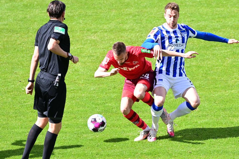 Schiedsrichter Deniz Aytekin (l.) hat beim Zweikampf zwischen Herthas Lukas Klünter (r.) und Kölns Dominik Drexler (M.) alles im Blick.