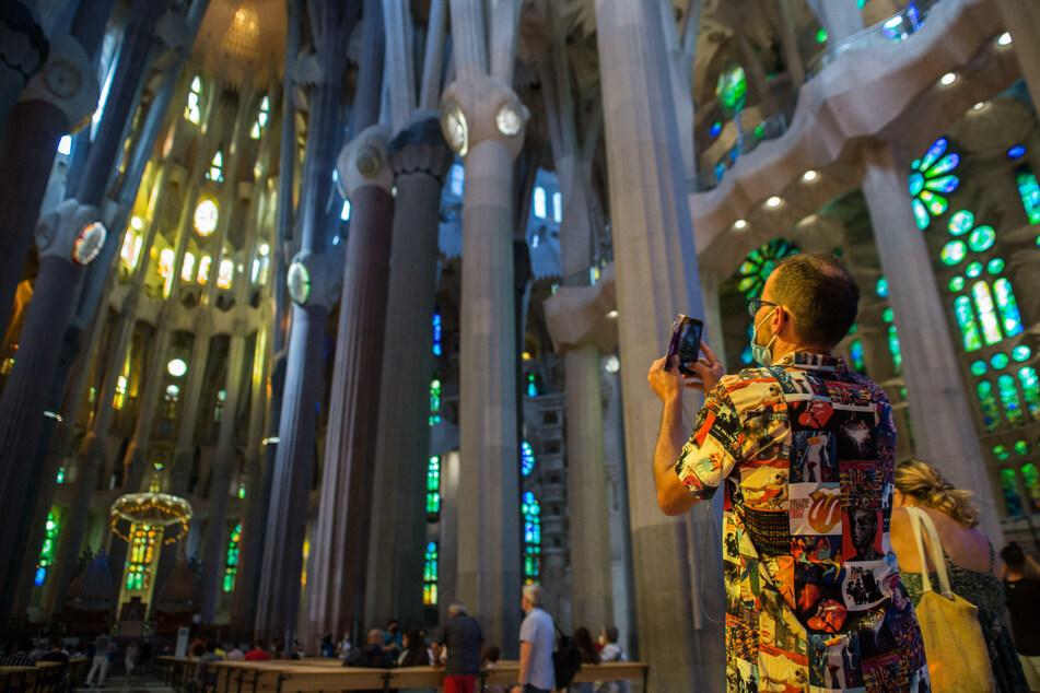Barcelona: Ein Mann mit Schutzmaske macht ein Foto während seines Besuchs in der Sagrada Familia. Die Kirche darf aufgrund der Corona-Pandemie nur von wenigen Menschen gleichzeitig betreten werden.