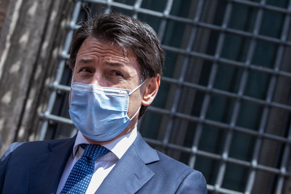Giuseppe Conte, Ministerpräsident von Italien, trägt einen Mundschutz während er mit einer Frau spricht, die ihn zu seinem Verhalten in der Corona-Krise beglückwünscht.