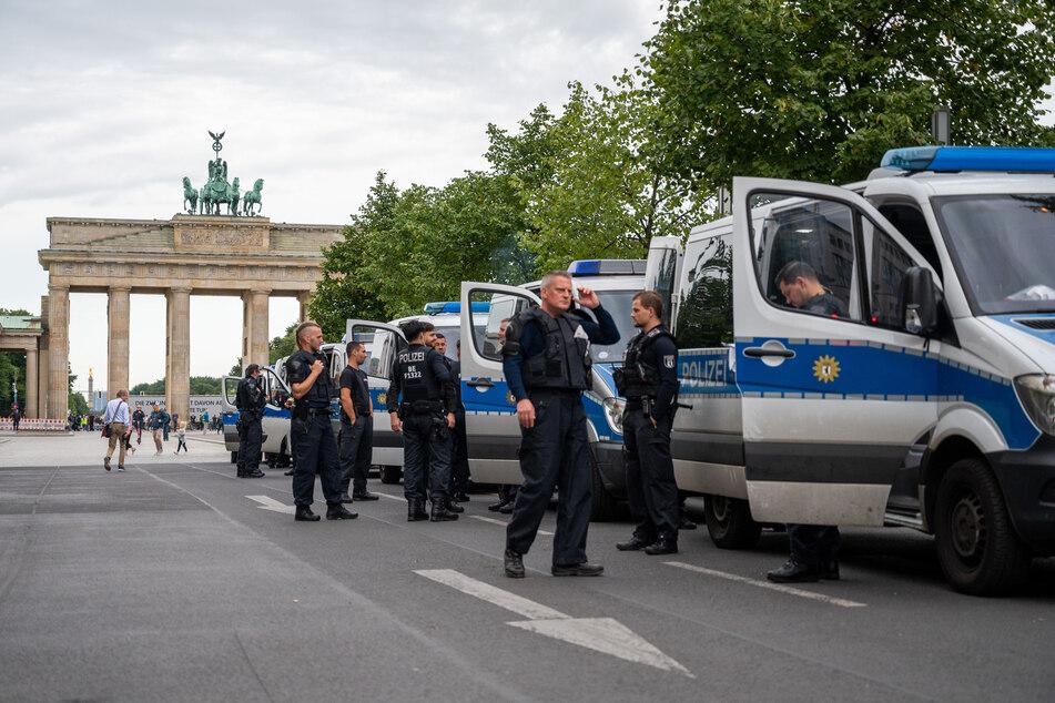 Polizisten stehen am frühen Morgen neben Polizeifahrzeugen vor dem Brandenburger Tor in Vorbereitung auf die heutigen Proteste gegen die staatlichen Corona-Maßnahmen.