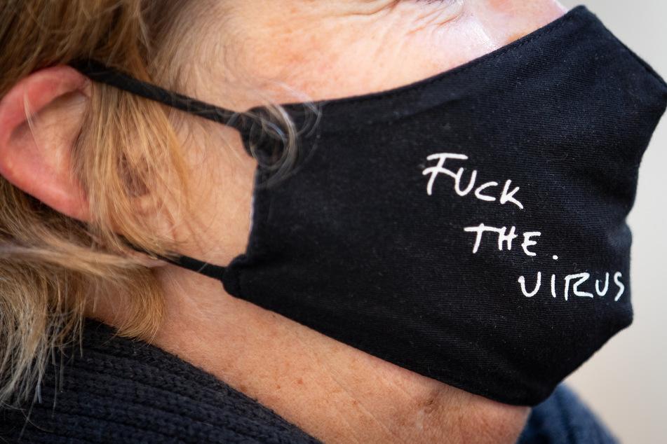 """""""Fuck The Virus"""" steht auf der schwarzen Mund-Nase-Bedeckung einer Frau."""