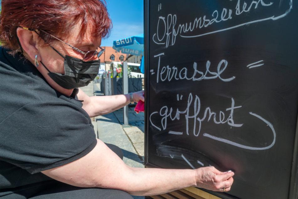 """Eine Frau schreibt """"Terrasse = geöffnet"""" vor einem Café in Tirschenreuth auf eine Hinweistafel."""