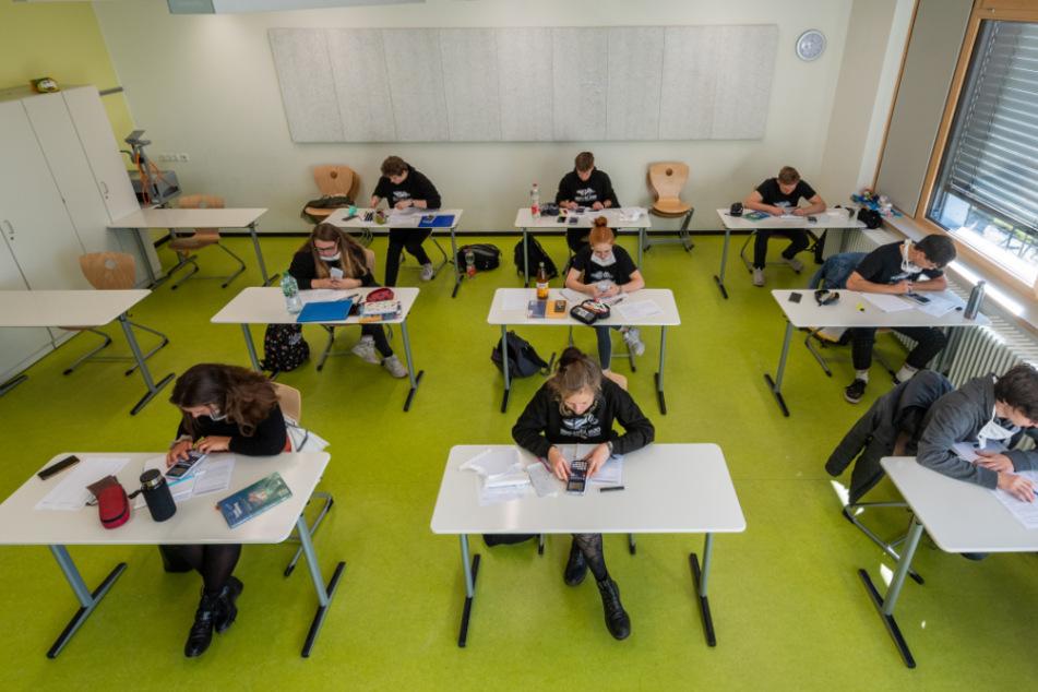 Schüler sitzen mit einem Abstand in einem Raum.