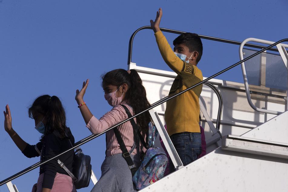 Flüchtlinge aus Griechenland winken in Athen, bevor sie ins Flugzeug nach Deutschland steigen.