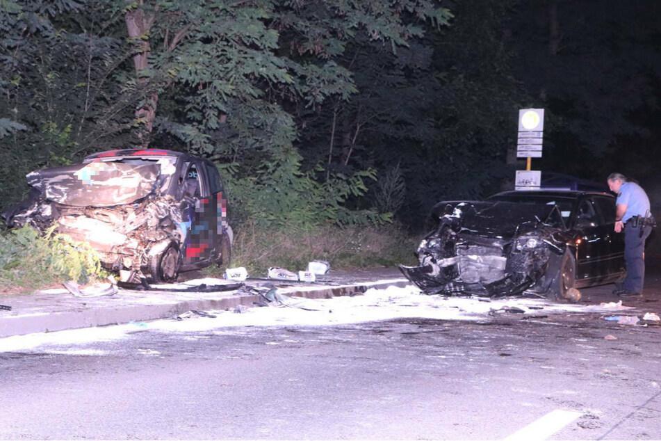 Ein Polizist untersucht das Wrack des Audi. Links im Bild ist der völlig zerstörte Wagen des Pizza-Lieferanten zu sehen.