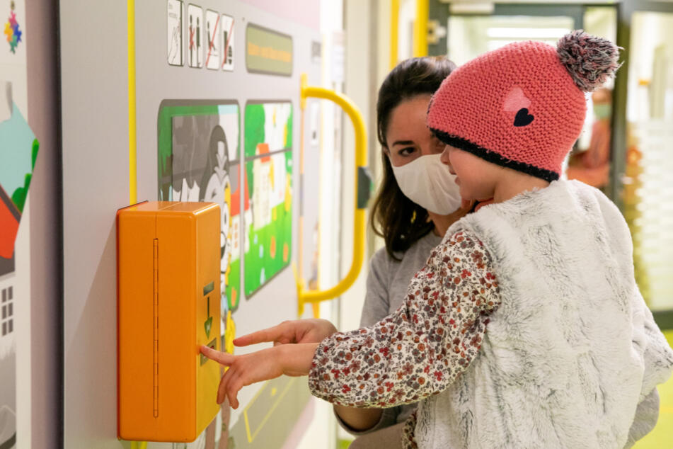 Mutter Linda Uhlmann (39) zeigt ihrer Tochter Mathilda (6) den Fahrkarten-Entwerter.