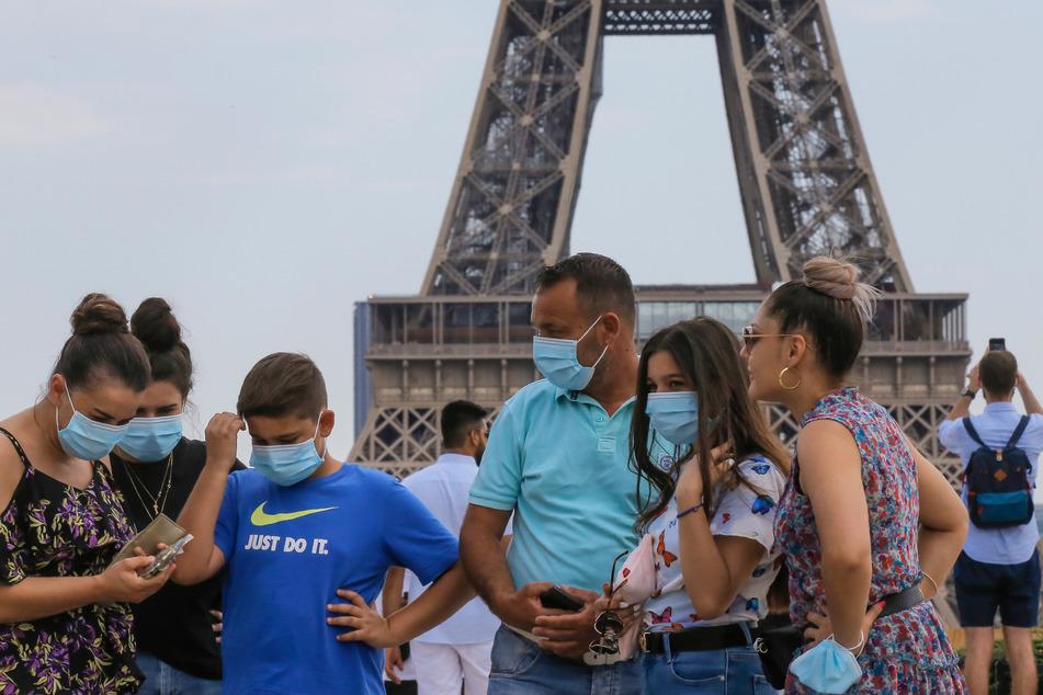 Eine italienische Familie trägt Mundschutze und steht auf dem Palais du Trocadéro mit Blick auf den Eiffelturm.