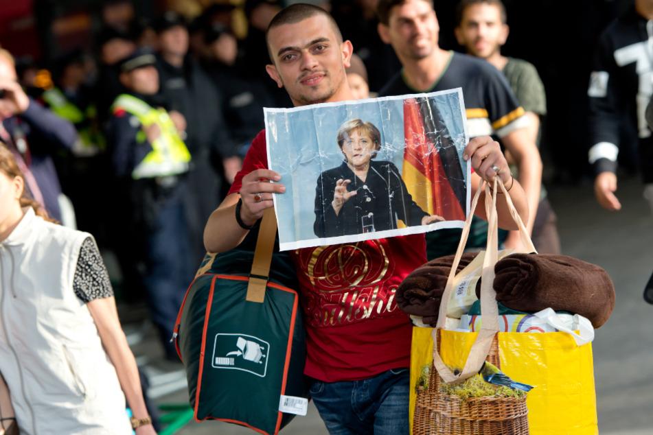 Bei seiner Ankunft im September 2015 in München hält ein Flüchtling ein Foto von Angela Merkel in den Händen.
