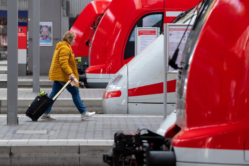 Eine Frau geht über dem Bahnsteig zu ihrem Zug.