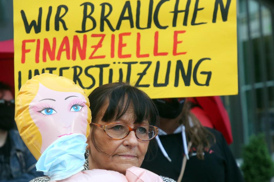 Berlin: Eine Teilnehmerin steht bei einer Protestaktion für die Öffnung von Prostitutionsstätten mit einer Sexpuppe im Arm nahe des Bundesrates. Bordelle litten und leiden unter der Corona-Krise.