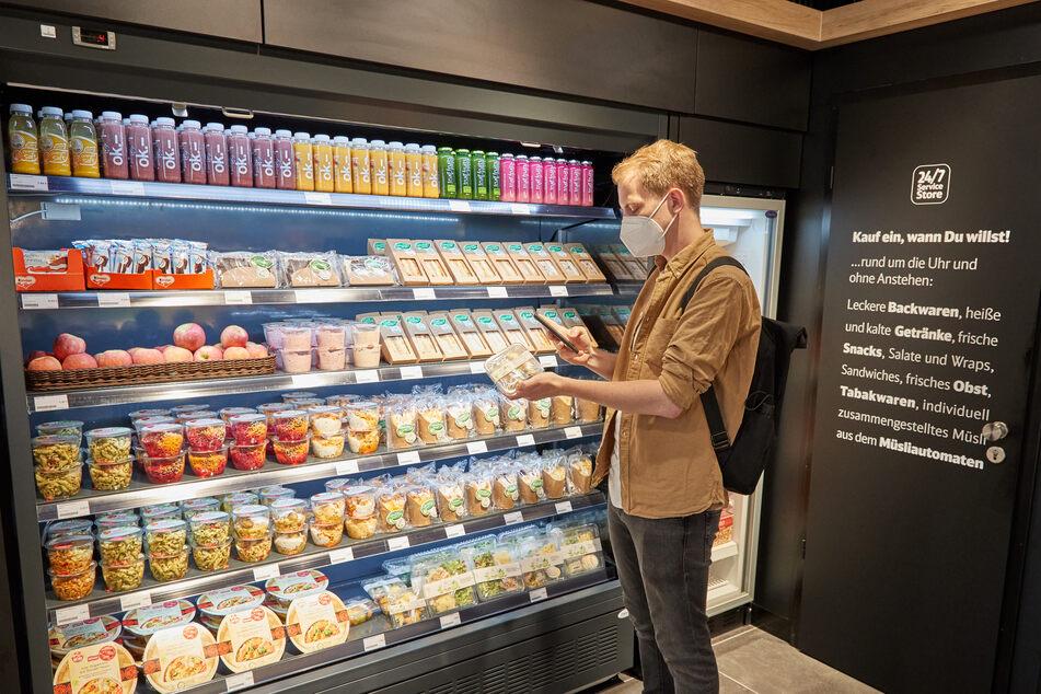 Ein Mitarbeiter demonstriert, wie Kunden die Waren mit dem Handy scannen können.