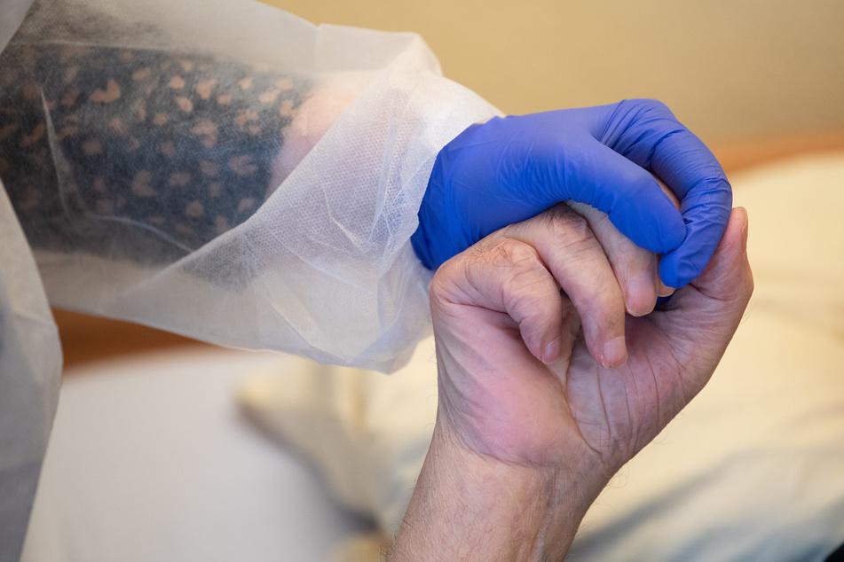 Eine Altenpflegerin in Schutzkleidung hält die Hand eines Bewohners. Die Zahl der Neuinfektionen steigt in Deutschland weiterhin an - auch immer mehr Todesfälle gibt es zu beklagen.