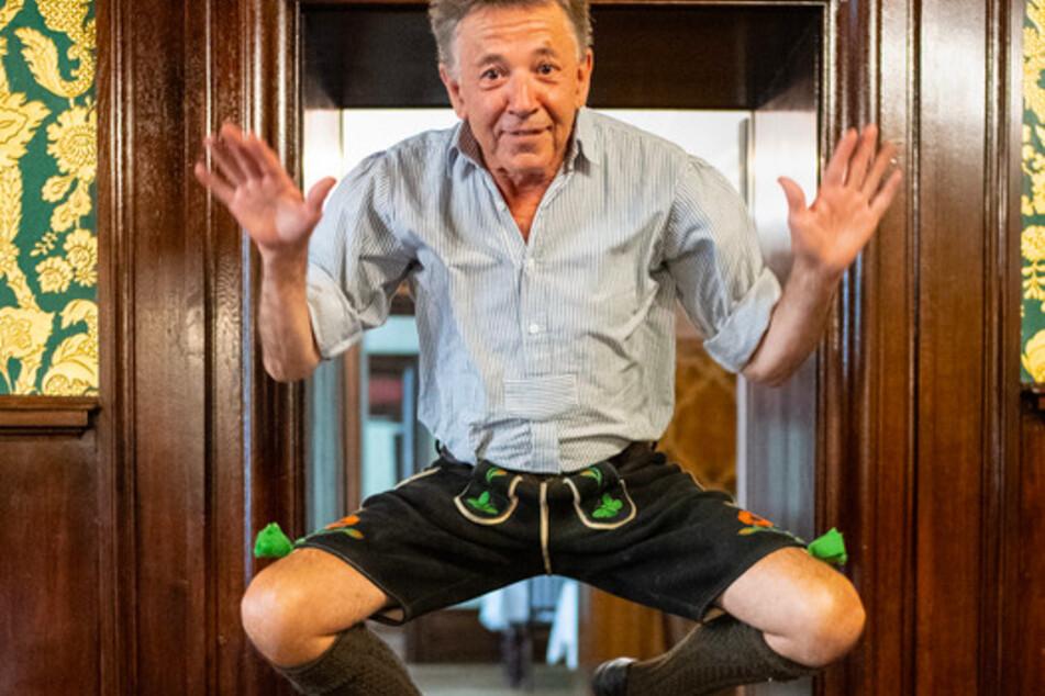 """Christoph """"Stofferl"""" Well, Musiker, zeigt im Rahmen eines Interviews in einem Wirtshaus einen Sprung, bei dem er sich auf die Schenkel klatscht."""