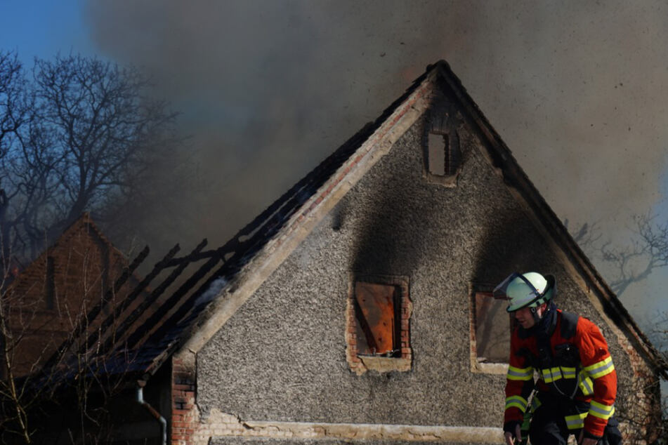 Ein Kamerad steht vor der ausgebrannten Scheune.