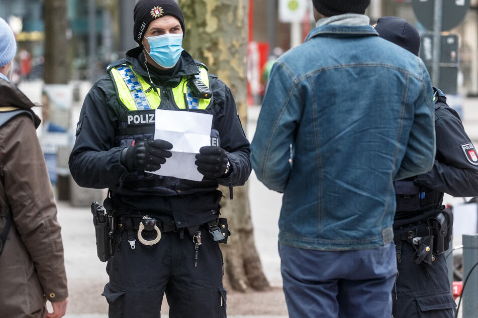 Polizisten sprechen in der Hamburger Innenstadt Passanten an, die ohne eine Mund-Nase-Bedeckung unterwegs sind. (Archivbild)