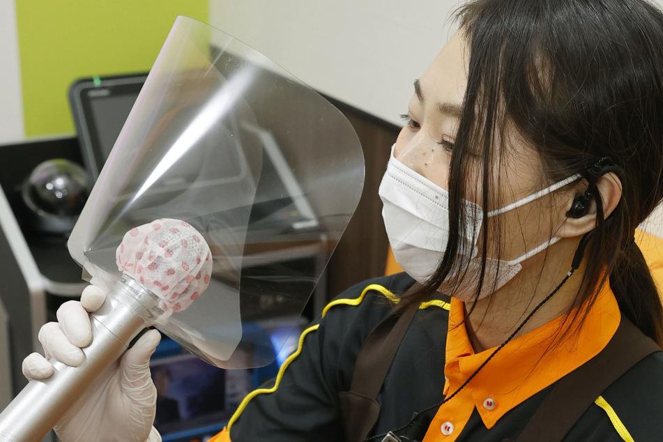 Eine Mitarbeiterin einer Karaoke-Bar hält ein Mikrofon in der Hand, welches mit Stoff und einem Hygieneschutz aus Plastik abgedeckt ist, um Infektionen mit dem Coronavirus zu verhindern.