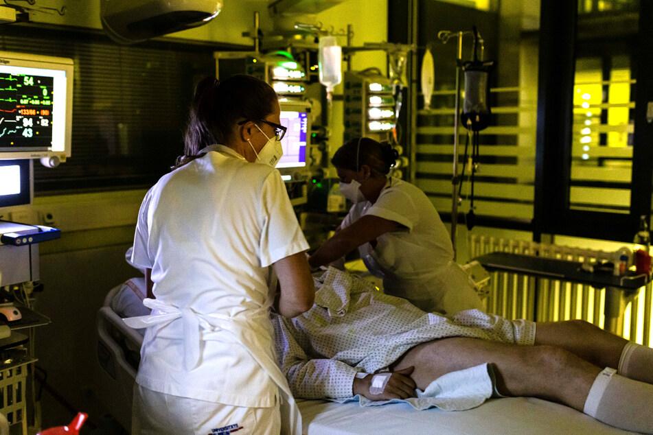 Elke Koch (l.), stellvertretende Stationsleiterin einer Intensivstation des Uniklinikums Freiburg, hilft einer Kollegin beim Aufrichten eines Patienten.