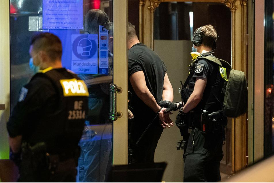 """Ein Polizeibeamter hält einen gefesselten Mann im Hotel """"Panorama"""" in der Nähe des Kurfürstendamms."""