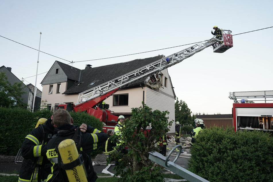 Feuerwehrleute sichern ein Wohnhaus, nachdem ein Kleinflugzeug am Samstag in das Dach gestürzt ist.