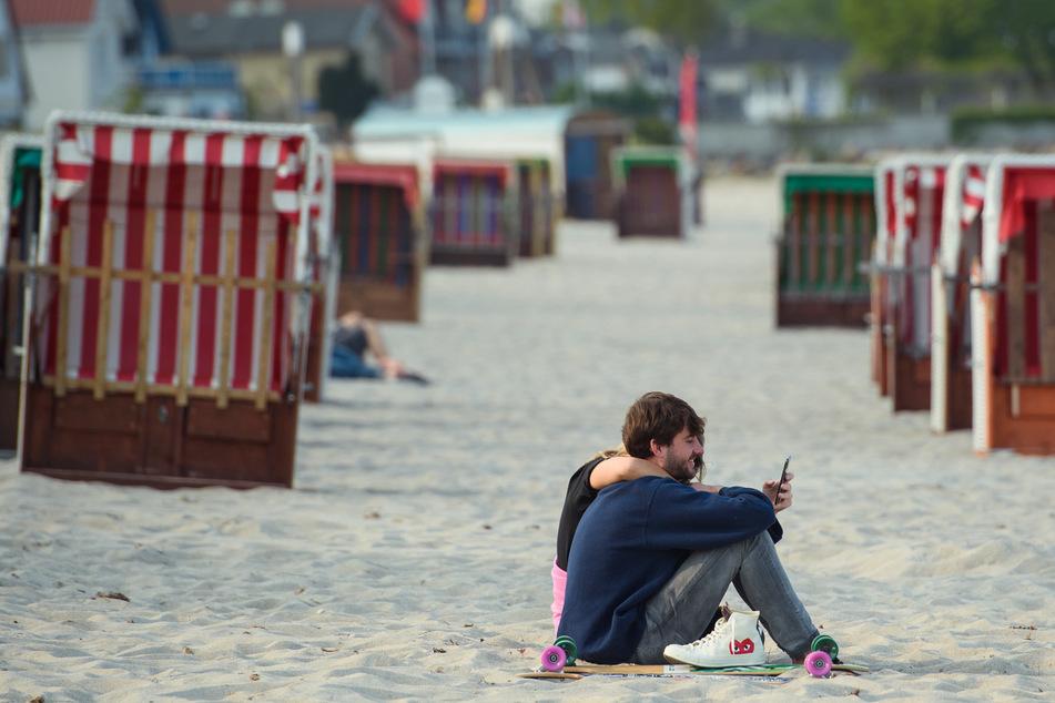 Schleswig-Holstein, Scharbeutz: Ein Paar sitzt im Sand vor zwei Reihen geschlossener Strandkörbe am Strand der Gemeinde Scharbeutz im Kreis Ostholstein.